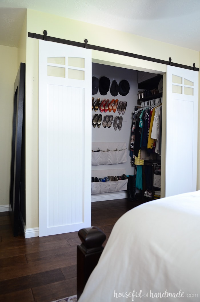 White closet sliding barn doors with window detail at the top in front of a closet with plywood storage organizers and hanging shoe storage.