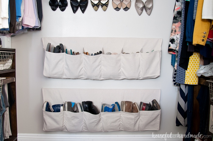 Inexpensive drop cloth hanging shoe storage on the wall in the closet filled with shoes.