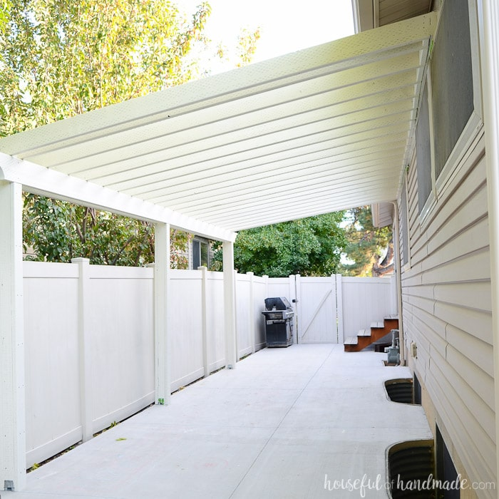 White painted patio pergola attached to the house with angled purlins.