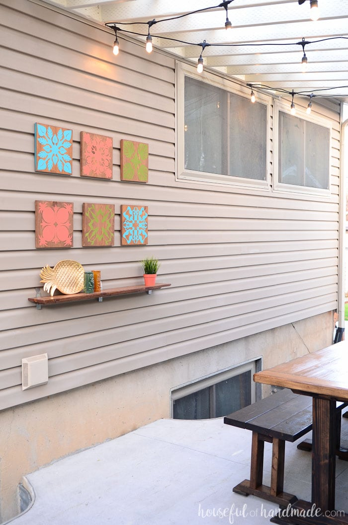 See how we turned our unused side yard into a tropical oasis. This beautiful tropical wall art helped add island decor to the large wall. Housefulofhandmade.com