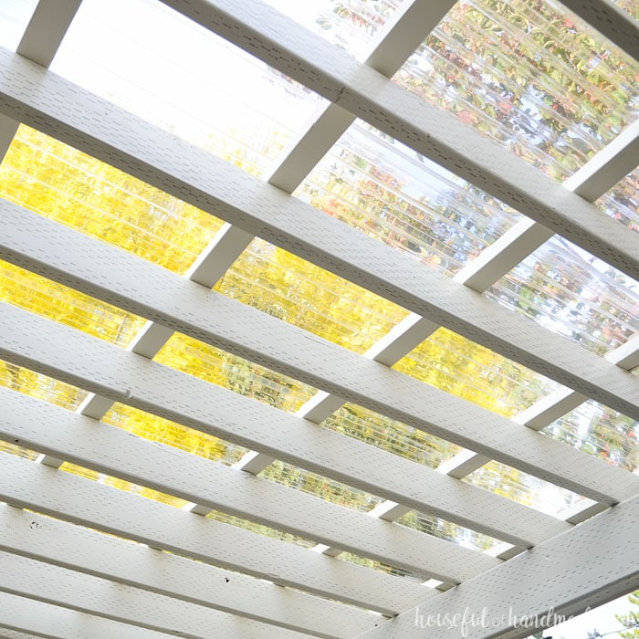 Looking up through a white painted pergola through the clear pergola roof.