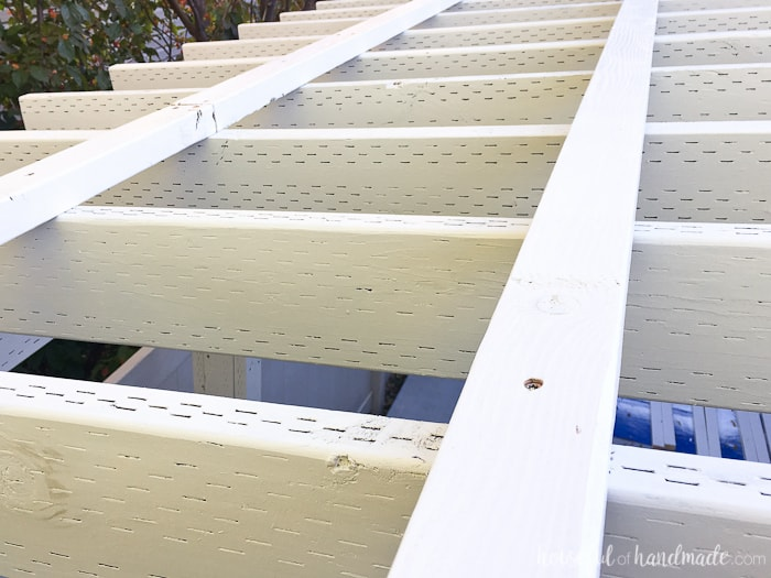 Secure 2x3 boards as purlins for the clear pergola roof. Get the full tutorial from Housefulofhandmade.com
