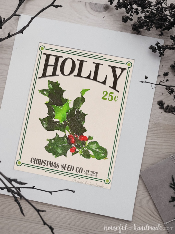 Holly printable Christmas art in a white mat on the table.