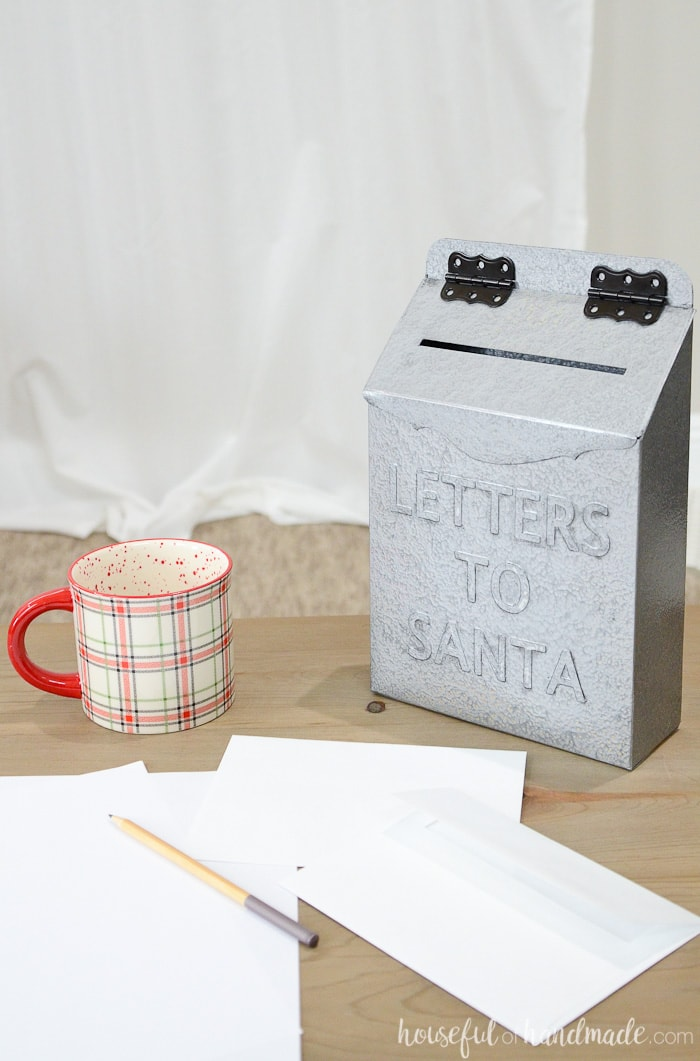Letters to Santa mailbox out of an old cereal box shown on table with coffee mug, pencil and papers