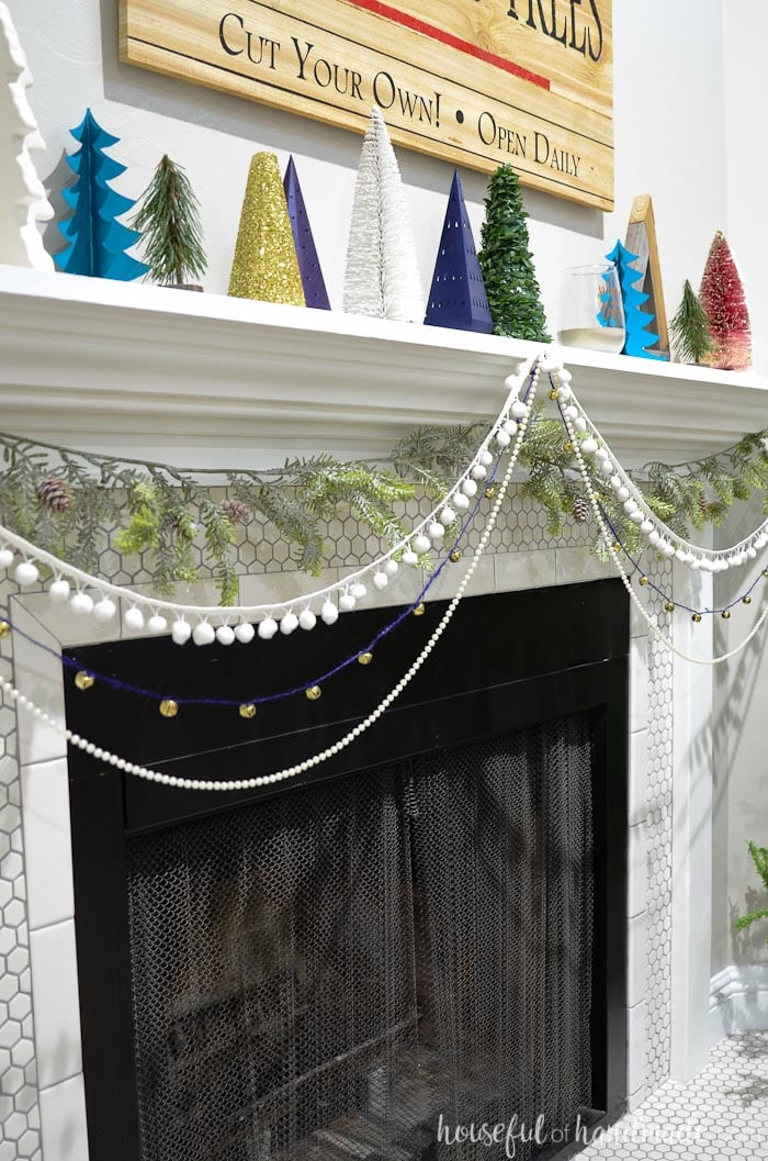 Add garlands to the front of your mantel for beautiful textures. Check out the entire holiday mantel at Housefulofhandmade.com.