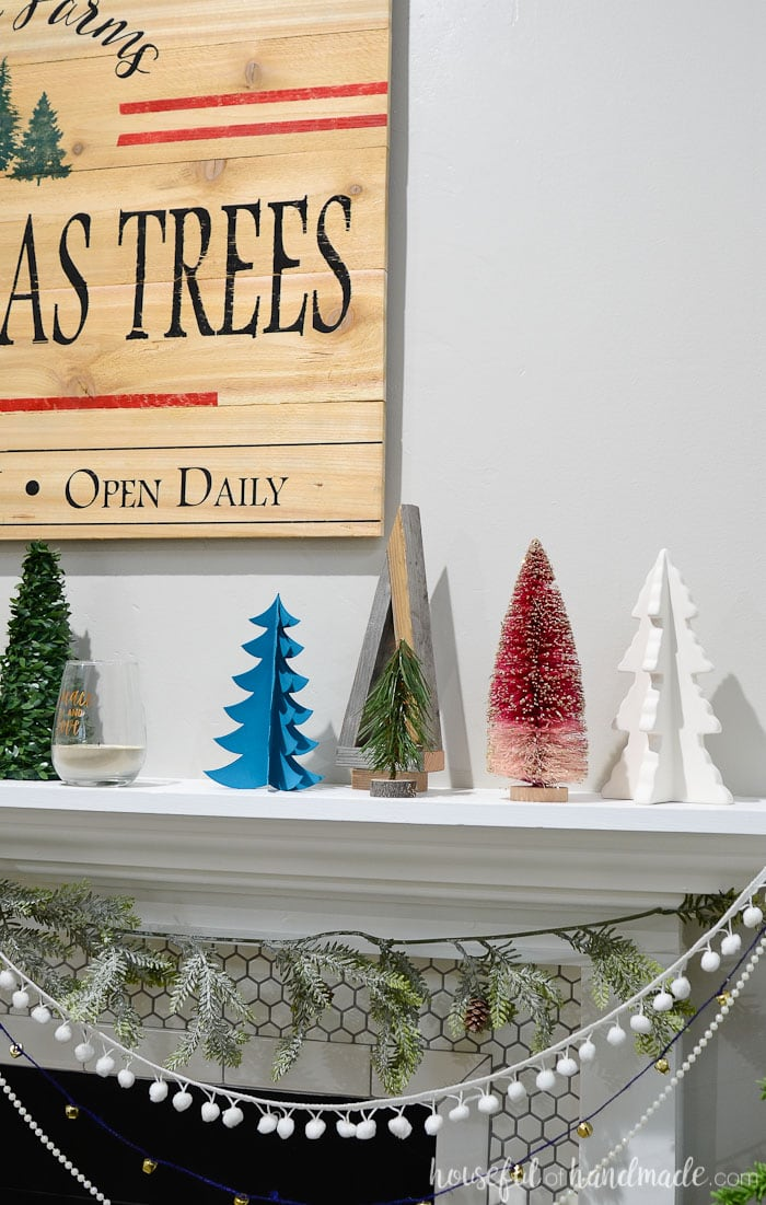 Create a beautiful holiday mantel on a budget with these ideas. A variety of Christmas trees and a beautiful DIY wood sign. Housefulofhandmade.com