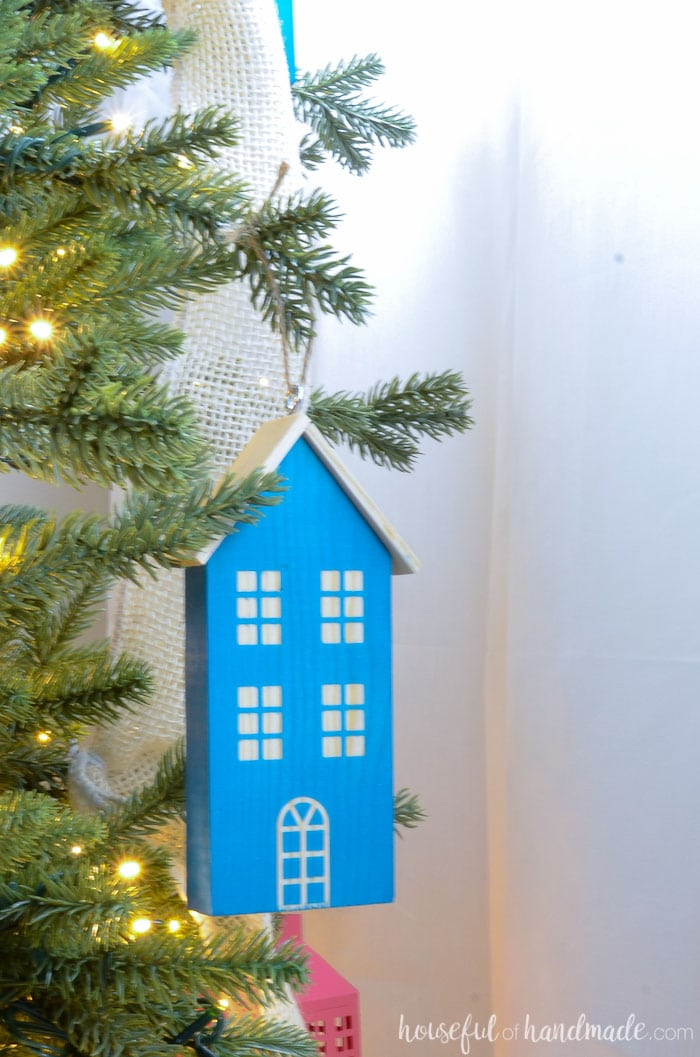 Turn scrap wood into adorable wooden houses for your Christmas tree. I love this colorful farmhouse Christmas tree. Housefulofhandmade.com