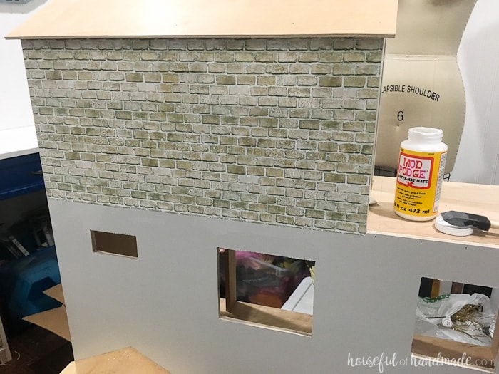 Add faux brick to the dollhouse exterior with Mod Podge. It looks fantastic and is budget friendly. Housefulofhandmade.com