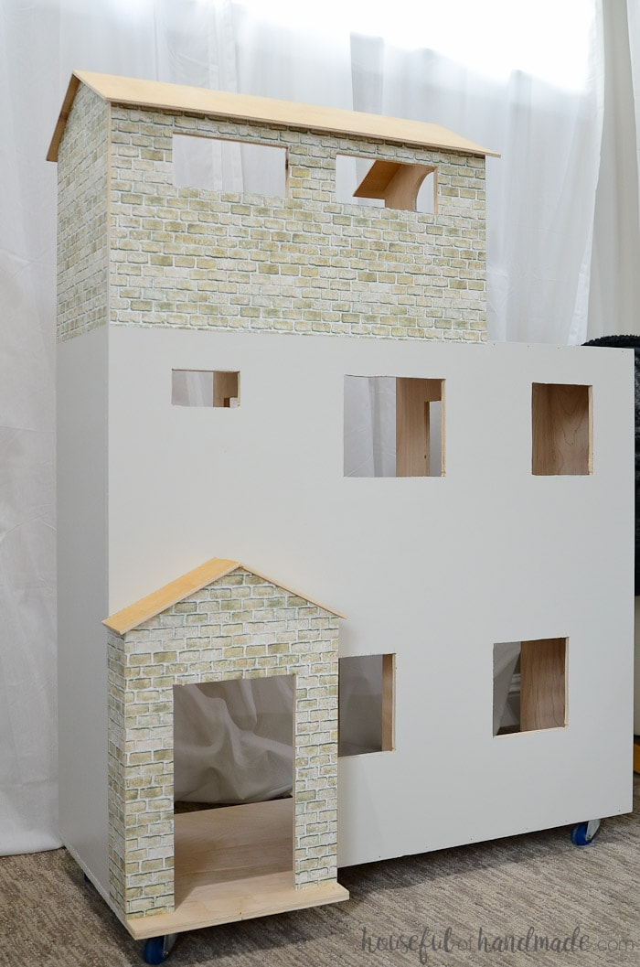 Handmade dollhouse painted white with brick