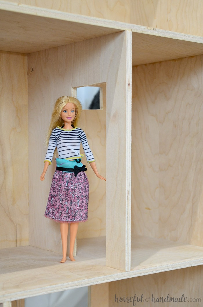 Beautiful handmade dollhouse shown with barbie on shelf