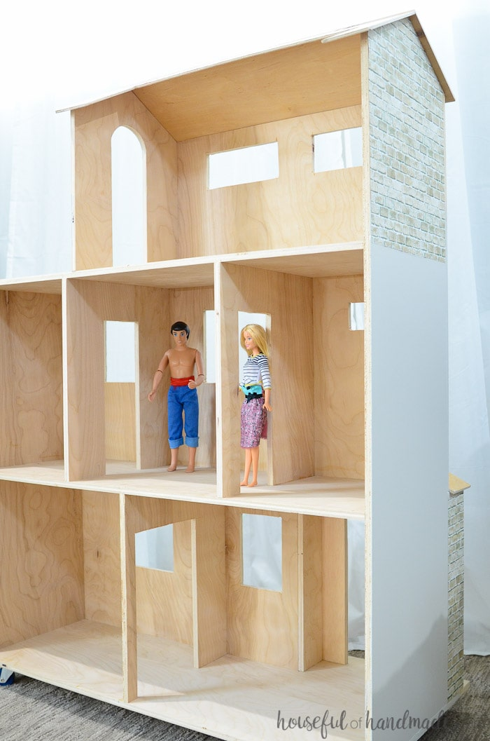 large handmade dollhouse shown with two barbie dolls shown inside