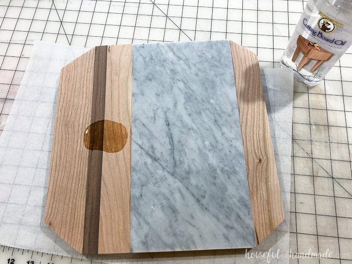 Adding the cutting board oil to the finished marble cheese board. Housefulofhandmade.com