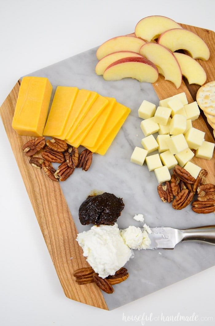 A marble cheese board is the perfect accessory for the holidays. This wood and marble cutting board is perfect for displaying your favorite cheese plate, appetizers, or as a DIY hostess gift. Housefulofhandmade.com