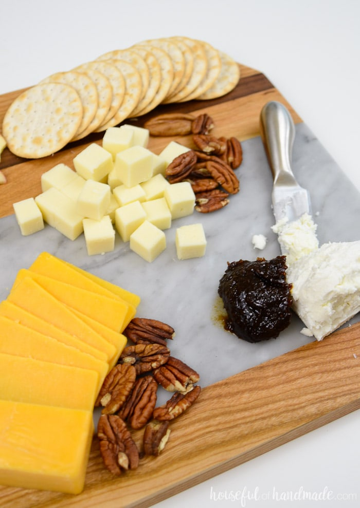 Create a super easy cheese plate with this beautiful homemade marble cheese board. It is so easy to make a wood and marble cutting board. housefulofhandmade.com