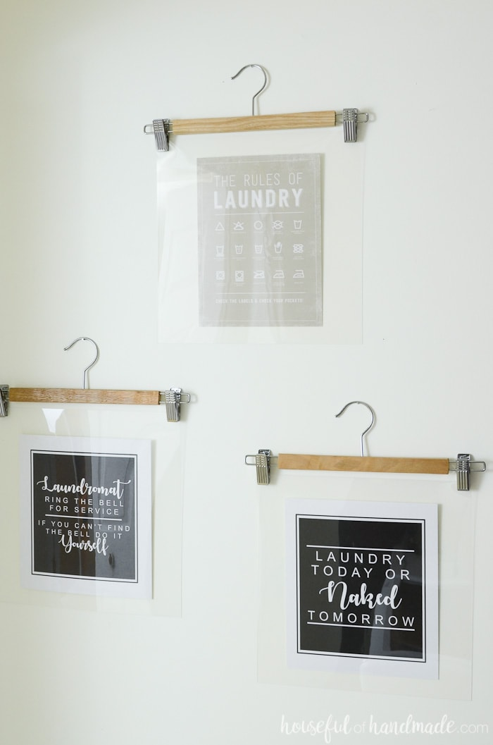Printables hung on the wall with wooden hangers in a farmhouse laundry room. Housefulofhandmade.com
