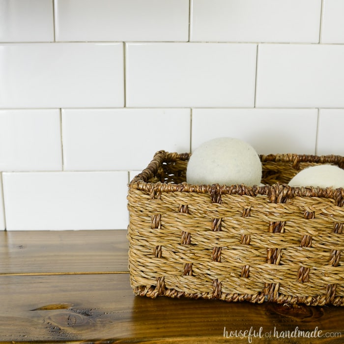 Dryer balls in a basket in the farmhouse laundry room. Housefulofhandmade.com