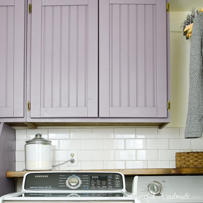 Purple painted beadboard cabinet doors with surface mounted hinges above a barnwood shelf behind a washer and dryer.