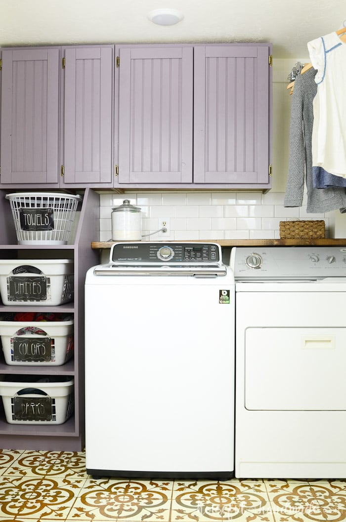 Farmhouse laundry room closet with stackable laundry basket storage and purple painted cabinets. Housefulofhandmade.com