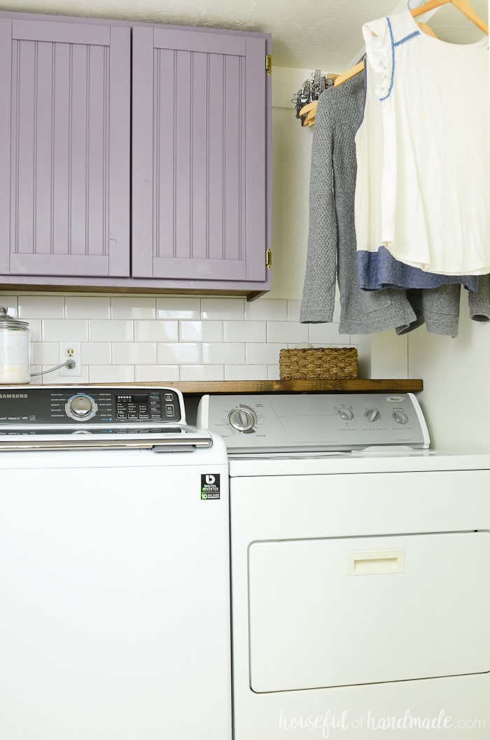 Colorful farmhouse laundry room reveal with purple cabinets and hanging clothes storage. Housefulofhandmade.com