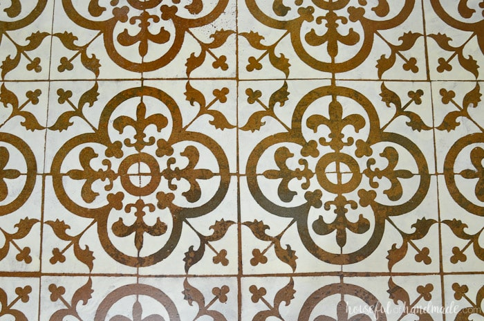 These faux patterned tiles were painted on a concrete basement floor. It looks so amazing and was transformed for only $19 with a floor stencil. Housefulofhandmade.com