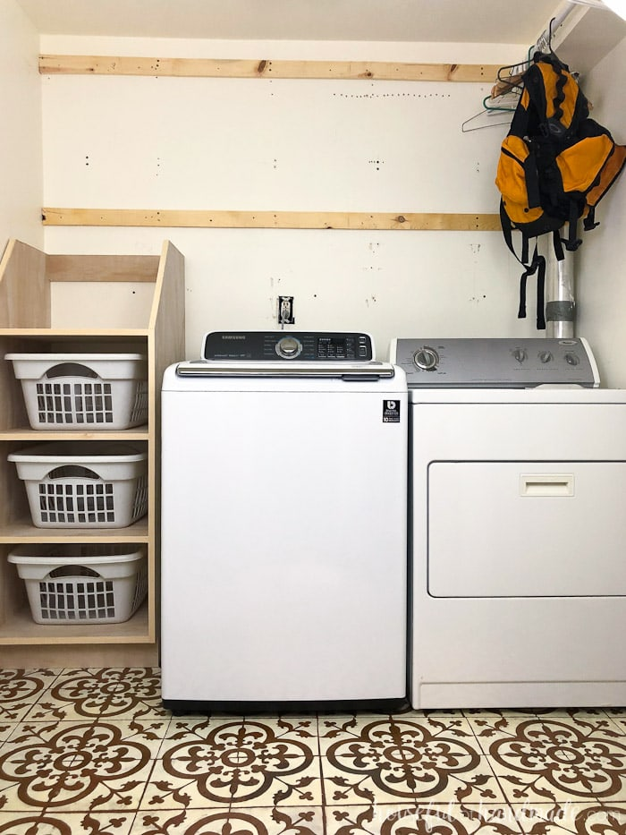 We are redoing our laundry room for only $100. This week we added stackable laundry basket storage. See the progress and get the build plans for this laundry room organizer at Housefulofhandmade.com.