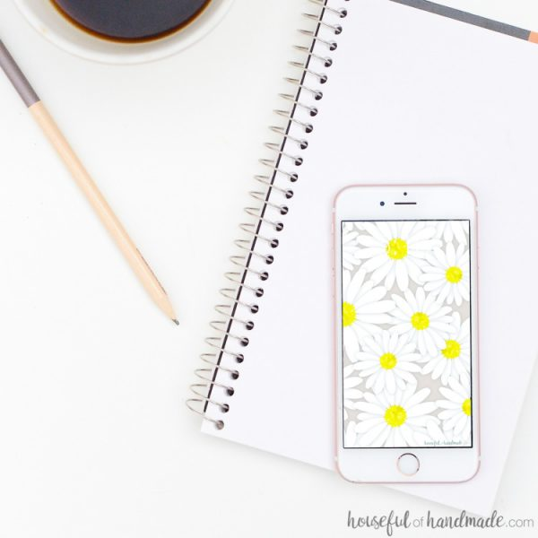 White smartphone with daisy print digital wallpaper on the screen. Housefulofhandmade.com