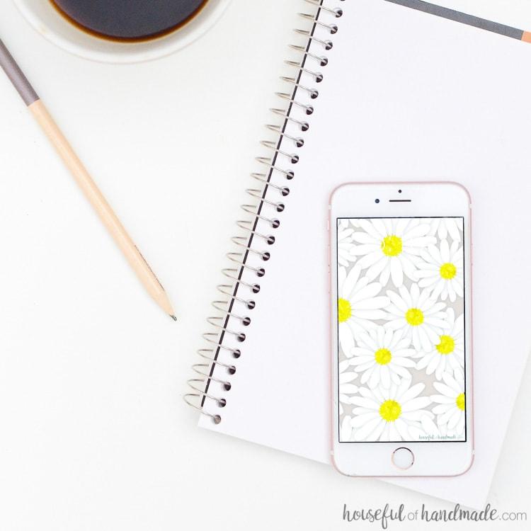 White smartphone with daisy print digital wallpaper on the screen. Housefulofhandmade.com