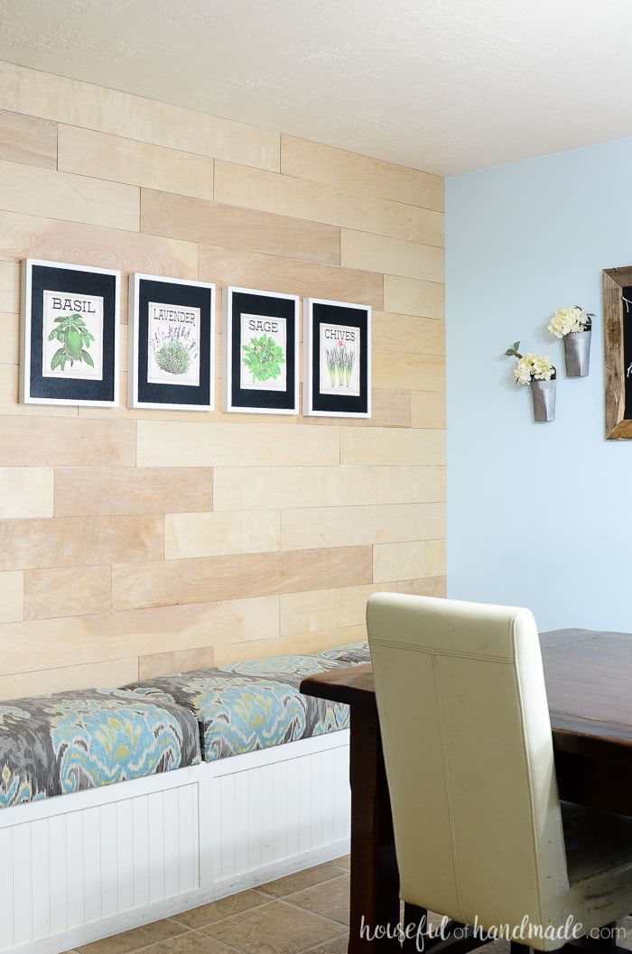 Wood wall with 4 framed herb prints over a bench. Dining room decor by Housefulofhandmade.com