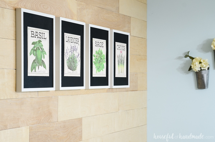 Four framed vintage seed packet herb prints in frames on a wood plank wall. Housefulofhandmade.com