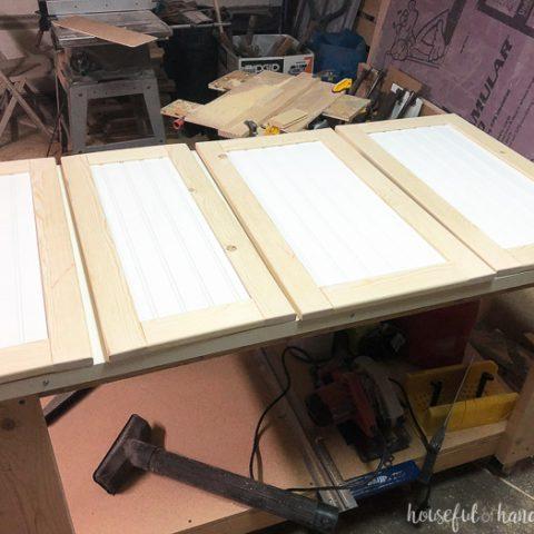 Four DIY shaker cabinet doors with beadboard panels in the workshop. Housefulofhandmade.com