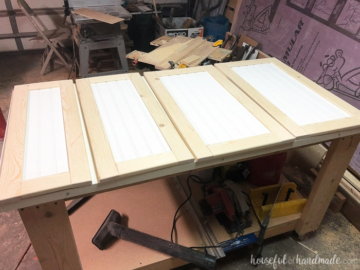 Four DIY shaker cabinet doors with beadboard panels in the workshop. Housefulofhandmade.com