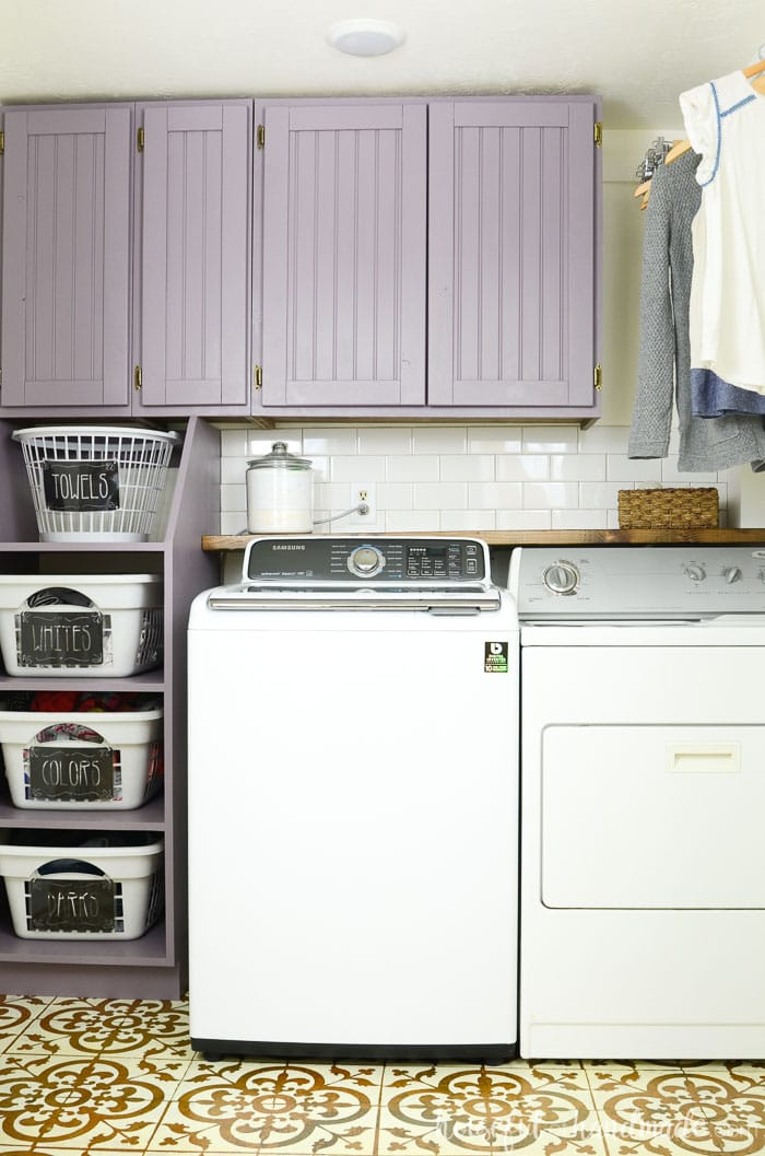 Purple DIY shaker cabinet doors over a washer and dryer with laundry basket storage on the side. Housefulofhandmade.com