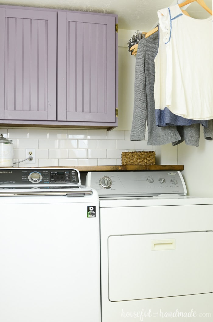 Laundry room with hanging clothing and purple cabinets that we were able to build cabinet doors cheap for! Housefulofhandmade.com