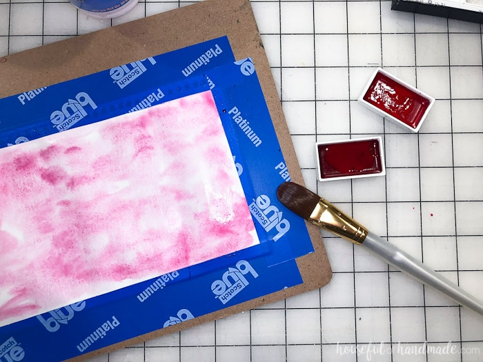 Piece of paper taped to a clip board with pink watercolor paint on it. Used to decorate a large glass candle holder. Housefulofhandmade.com