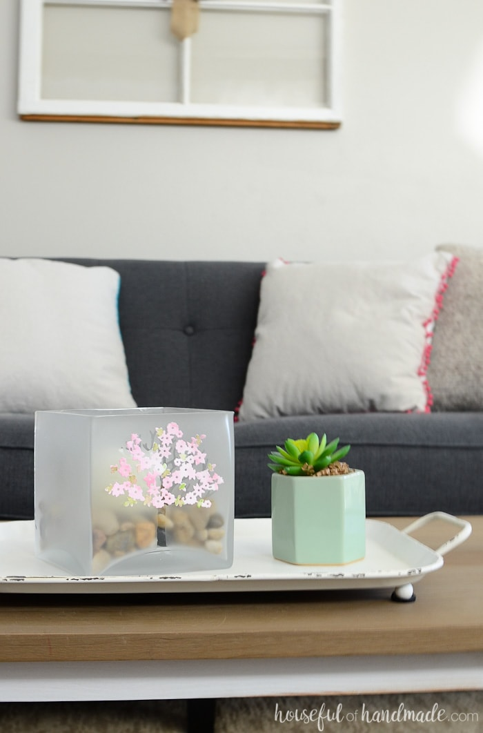 Coffee table with white tray and large glass candle holder with tree design. In front of a grayish-navy sofa with neutral pillows.