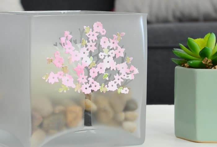 Large glass candle holder decorated with a frosted tree and spring blossoms on a tray in a living room. Housefulofhandmade.com