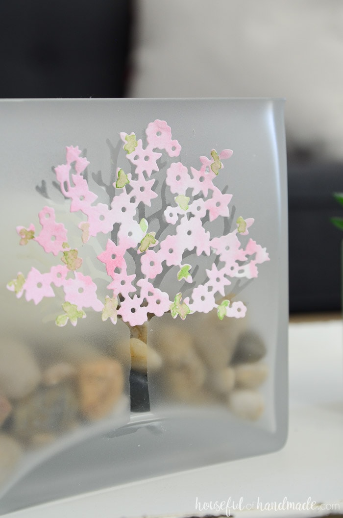 Frosted glass jar with etched tree design and watercolor spring blossoms filled with rocks and a candle. Housefulofhandmade.com