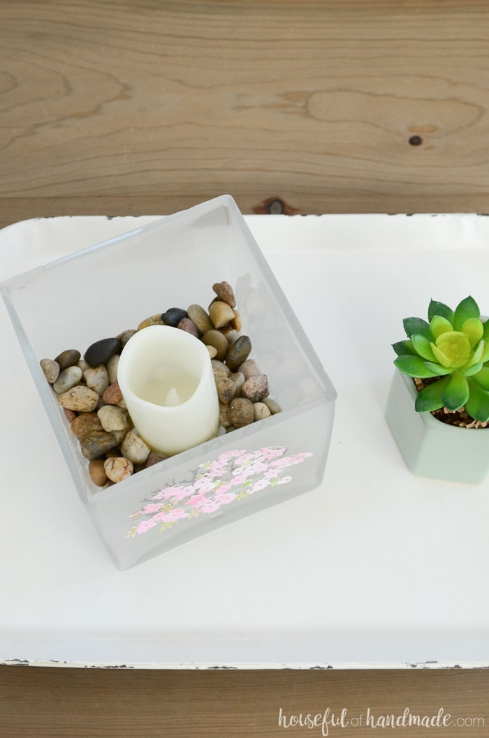 A square candle holder filled with rocks and a candle on a white tray. Housefulofhandmade.com