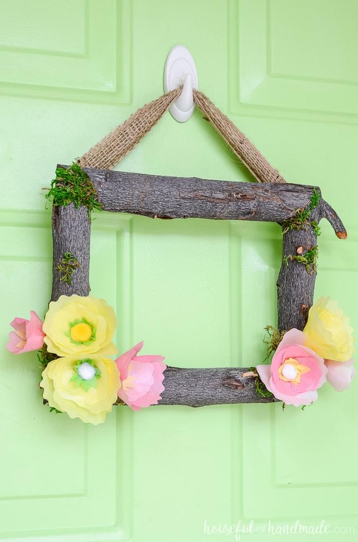 A beautiful spring flower wreath on a green front door. Housefulofhandmade.com