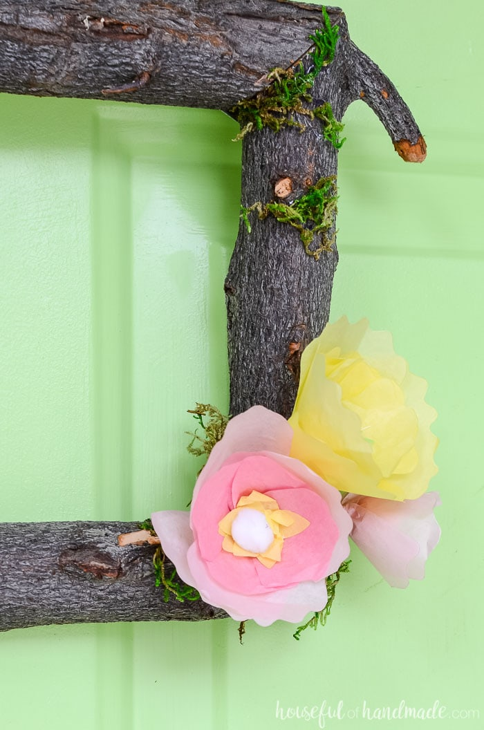 Yellow and pink flowers on a wreath made from tree branches on a green door. Housefulofhandmade.com