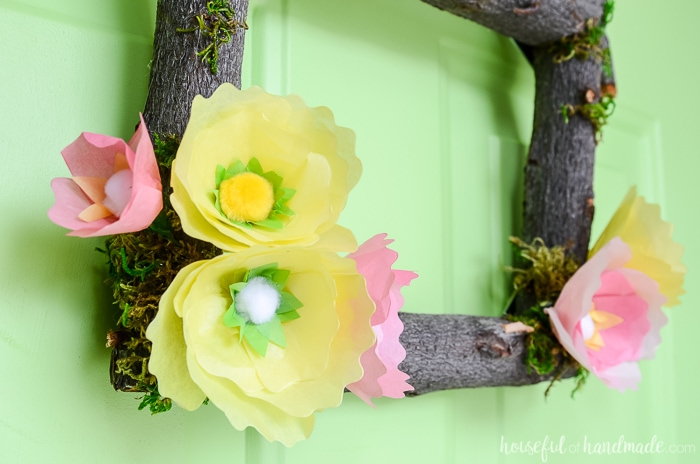 Create a beautiful spring flower wreath for the front door. Yellow and pink tissue paper flowers on a wreath frame made of logs. Housefulofhandmade.com
