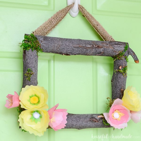 Square wreath made out of branches and tissue paper flowers to make a spring flower wreath. Housefulofhandmade.com
