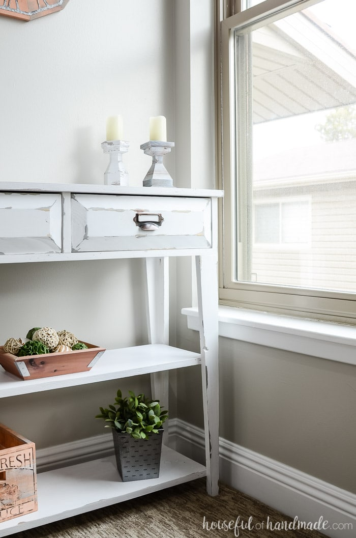 White farmhouse console table next to the window. The small console table has drawers and 2 shelves. Housefulofhandmade.com