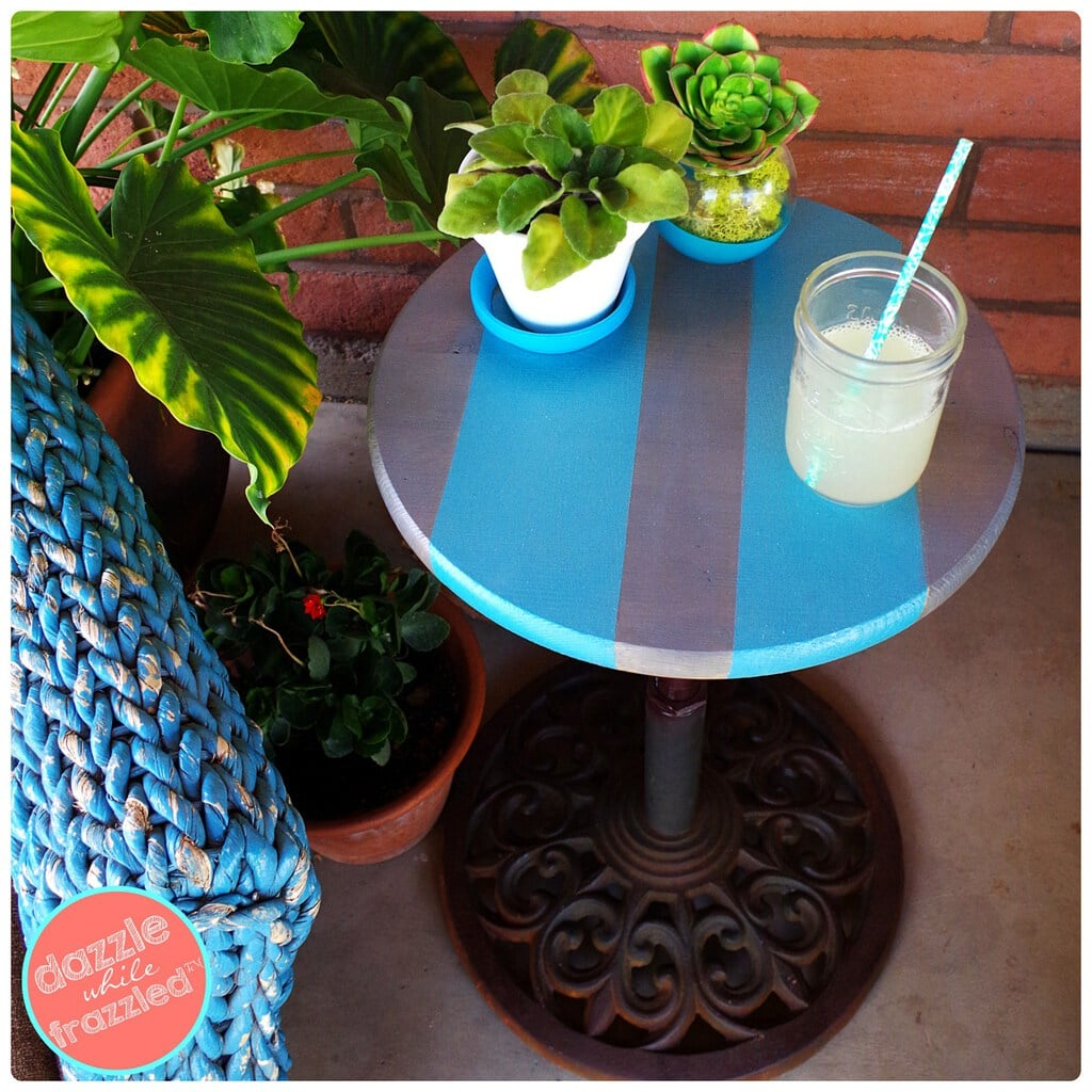 If you have an umbrella stand, but no longer have an umbrella, turn it into a side table instead of tossing it. Dazzle while Frazzled shares her adorable DIY Umbrella Stand into and Easy Patio Side Table.