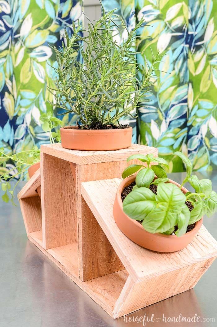 Three terra cotta pots holding herbs in a cedar countertop herb garden. Housefulofhandmade.com