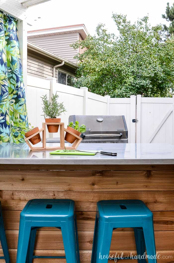 Outdoor kitchen island in front of a BBQ. Cedar countertop herb garden on top of the outdoor kitchen table. Housefulofhandmade.com
