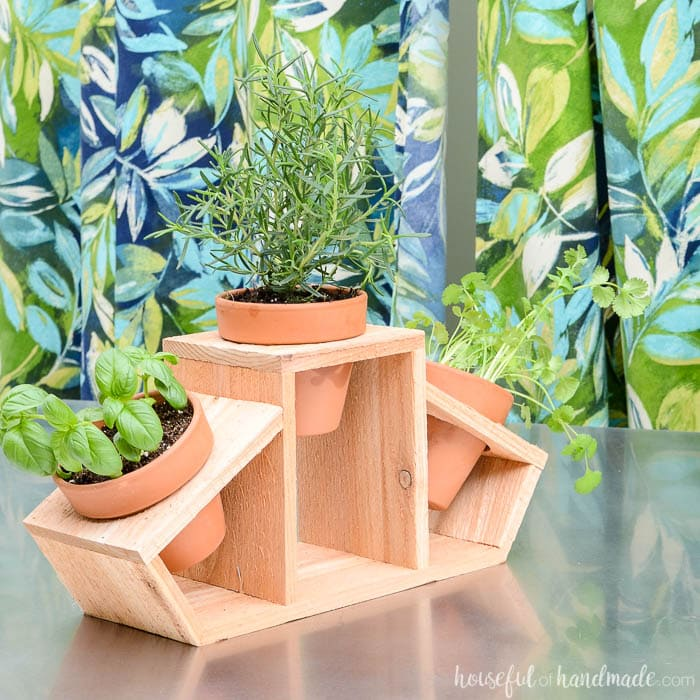 DIY countertop herb garden made with a cedar fence picket and 3 clay pots.