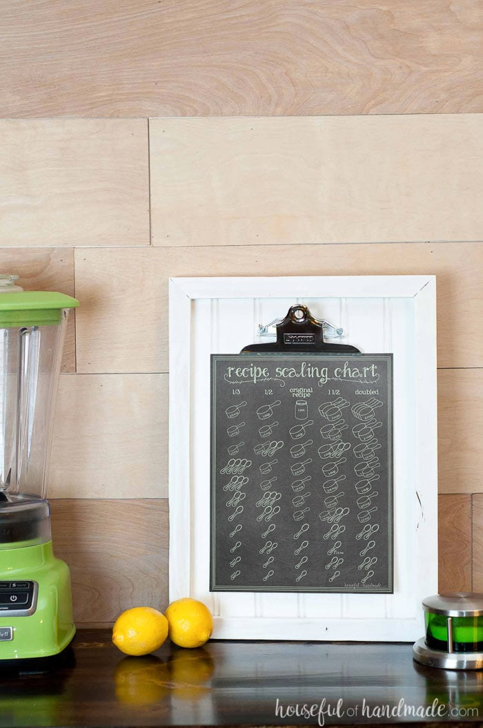 Chalkboard design recipe scaling chart with instructions on how to 1/3, half, 1 1/2, or double a recipe. Hanging on a clipboard picture frame in the kitchen. Housefulofhandmade.com