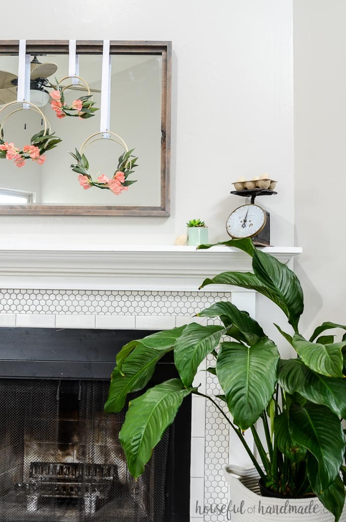 Simple mantel decor for spring consists of floral embroidery hoop wreaths hung on a gray rustic mirror. Housefulofhandmade.com
