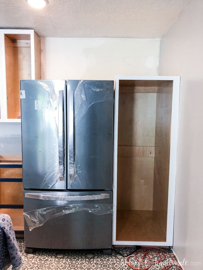 The new stainless steal fridge is in place next to the DIY pantry cabinet. Housefulofhandmade.com